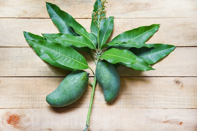 Fresh green mango and green leaves on wood Premium Photo