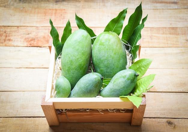 Fresh green mango and green leaves on wooden box Premium Photo
