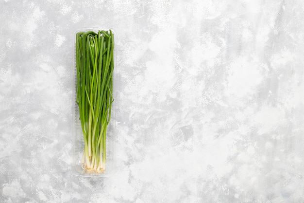 Fresh green onions in plastic box on grey concrete Free Photo