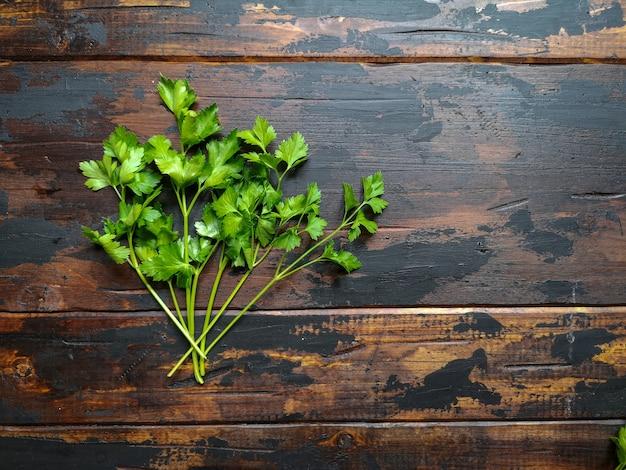 新鮮な緑のパセリ、コリアンダーの素朴な木製のテーブル。 Premium写真