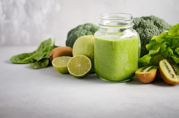 Fresh green smoothie in a jar with ingredients on a gray concrete background, selective focus. Premium Photo