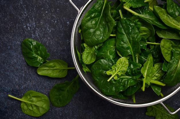 Fresh green spinach leaves on a dark concrete background Premium Photo