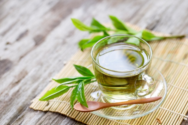 Fresh green tea with tea leaves in the water on wood table Premium Photo