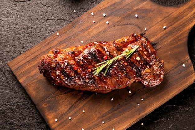 Свежее мясо на гриле. стейк из говядины на гриле средней прожарки на деревянной доске. вид сверху. Premium Фотографии
