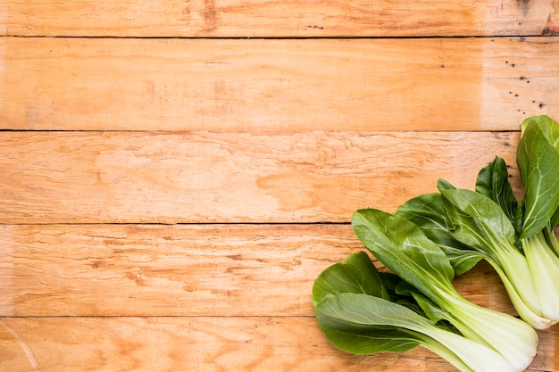 Fresh harvested bokchoy on the corner of the wooden table Free Photo