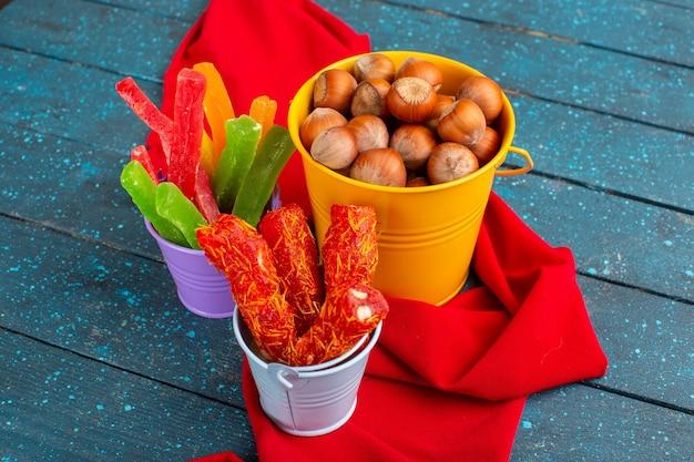 Nocciole fresche con torrone e marmellata su blu Foto Gratuite