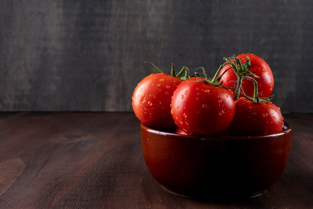 Fresh and health tomatoes in ceramic bowl on brown stone surface Free Photo