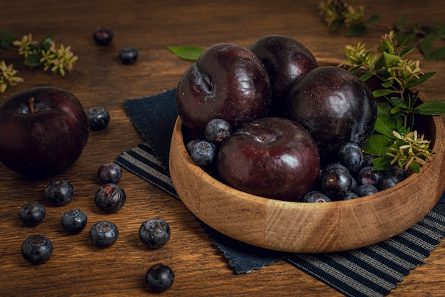 Fresh healthy bowl full of plums and blueberries Free Photo