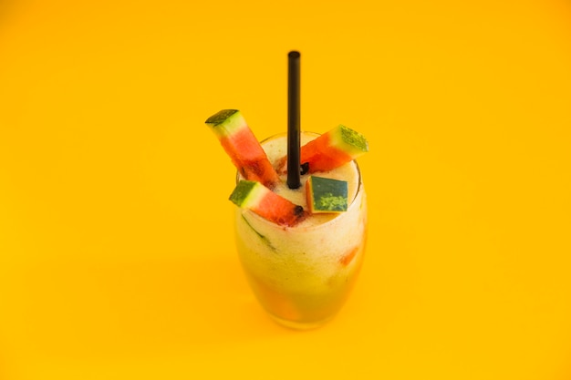 Fresh healthy cocktail with watermelon slice on yellow backdrop Free Photo
