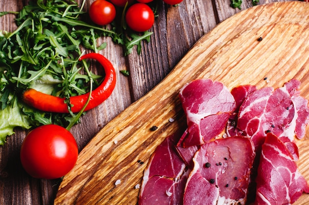 Fresh and healthy food. sliced red meat lies on the wooden table with arugula Free Photo
