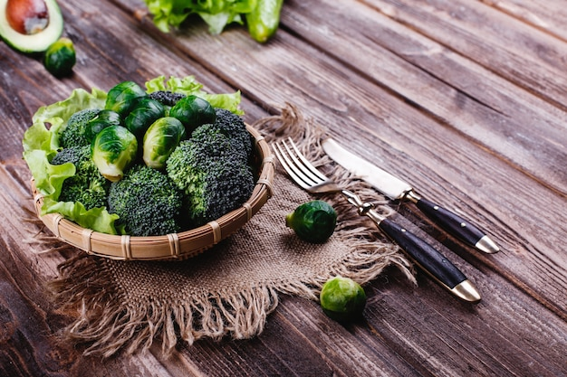 Fresh and healthy food. wooden bowl with broccoli, brussel sprouts, olive oil, green pepper Free Photo