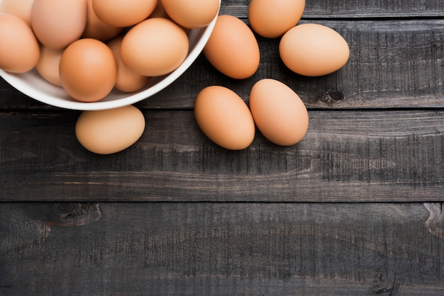 Fresh hen egg in white bowl and 6 hen egg out side on black color wood table Premium Photo
