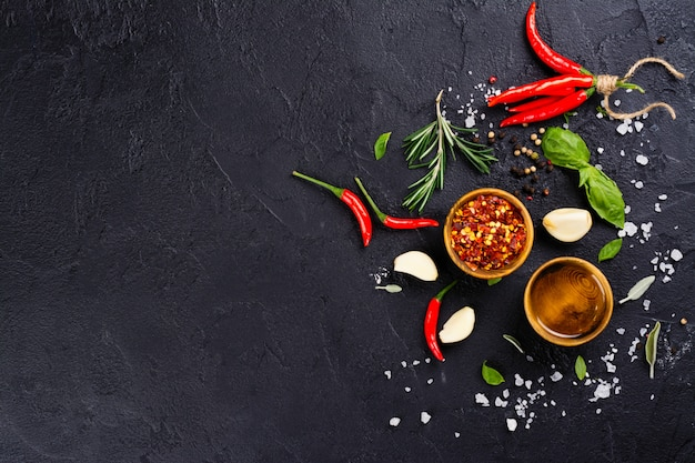 Fresh herbs and spices on black stone table Premium Photo