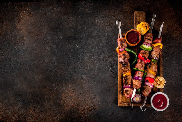 Fresh, home-cooked on the grill fire meat beef shish kebab with vegetables and spices, with barbecue sauce and ketchup, on a dark background on a wooden cutting board above copy space Premium Photo