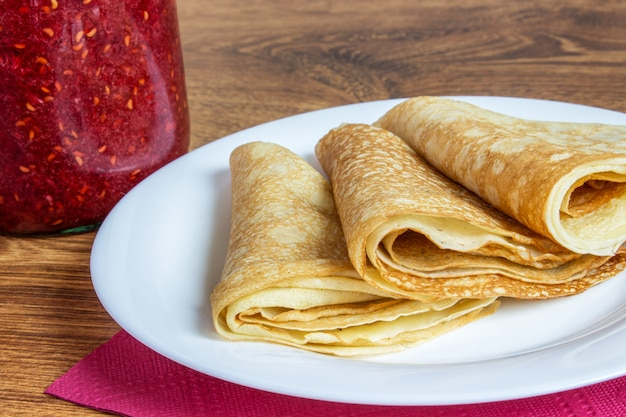Fresh homemade folded crepe filled with strawberry jam on plate Premium Photo