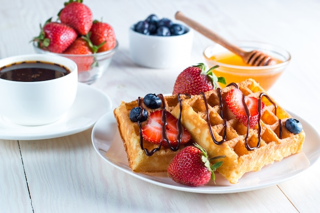 Fresh homemade food of berry belgian waffles with honey, chocolate, strawberry, blueberry, maple syrup and cream. healthy dessert breakfast concept with juice Premium Photo
