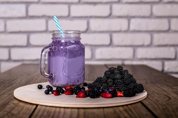 Fresh homemade yogurt smoothie wild berries in a glass jar on an old vintage , closeup, selected focus. harvest . Premium Photo
