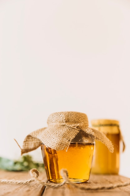 Fresh honey in closed jar on wooden surface Free Photo