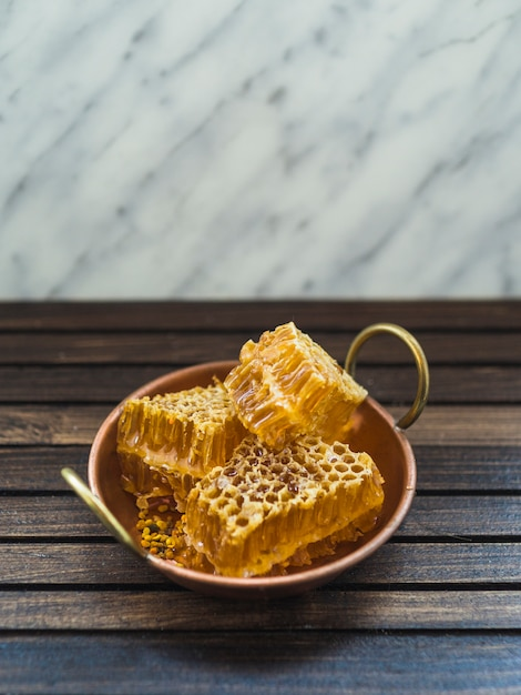 Fresh honey comb pieces in copper utensil on wooden table Free Photo