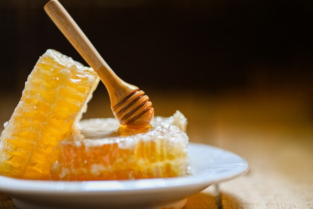 Fresh honey healthy food yellow sweet honeycomb slice with wooden dipper on plate and dark Premium Photo