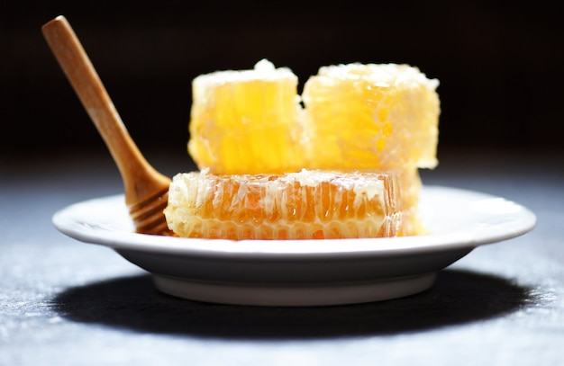 Fresh honey healthy food yellow sweet honeycomb slice with wooden dipper on white plate Premium Photo