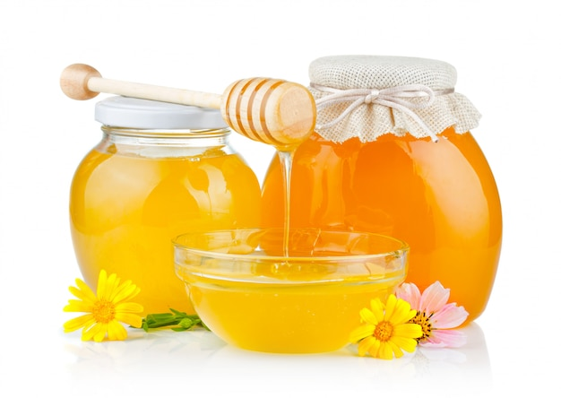 Fresh honey with dipper and flowers isolated Premium Photo