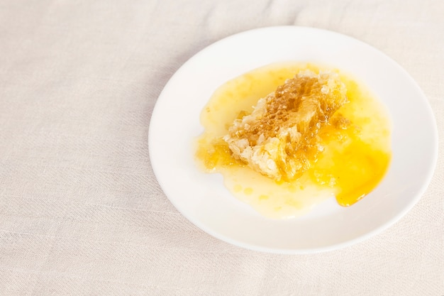 Fresh honeycomb on white ceramic plate over table cloth Free Photo
