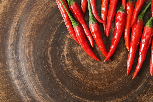 Fresh hot peppers on brown clay plate. Premium Photo