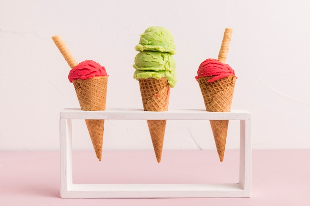 Fresh ice cream scoop in cones with waffle straw on stand Free Photo
