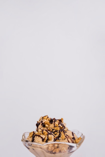 Fresh ice cream with nuts and topping in glass bowl Free Photo