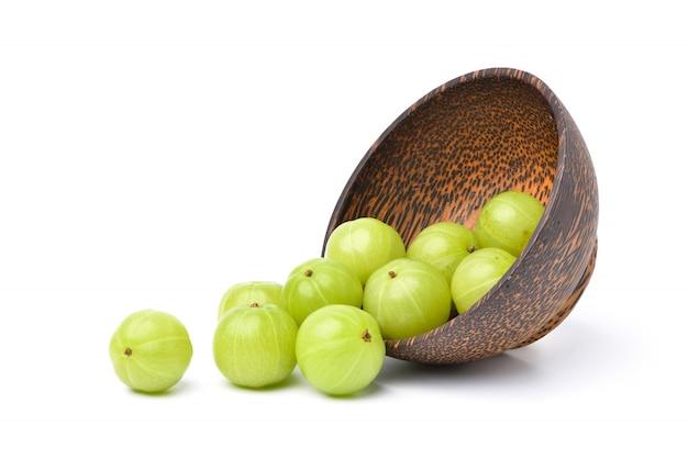 Fresh indian gooseberry fruits in wooden bowl on white. Premium Photo