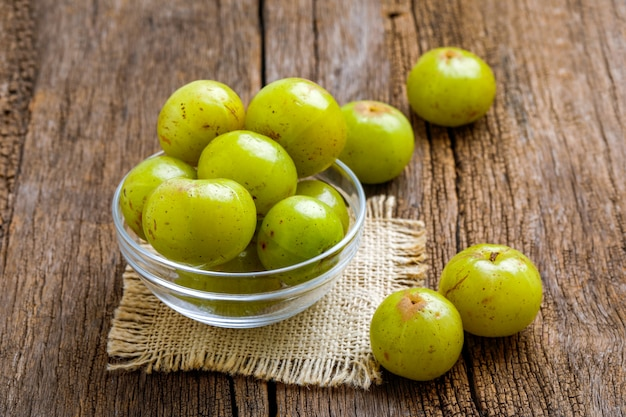 Fresh indian gooseberry in glass bowl  on wooden board Premium Photo