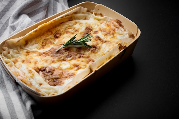Fresh italian lasagna and table cloth on kitchen counter Free Photo