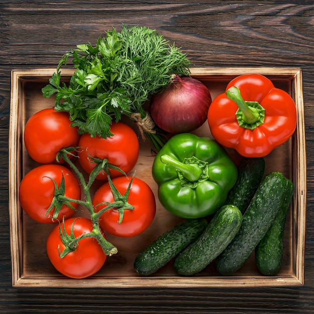 Fresh and juicy vegetables in a wooden box. vegetable salad ingredients. cucumbers, tomatoes, paprika, onions, herbs Premium Photo