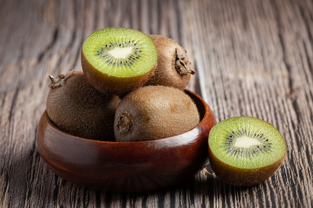 Fresh kiwi, cut into half, put on a wooden bowl Free Photo