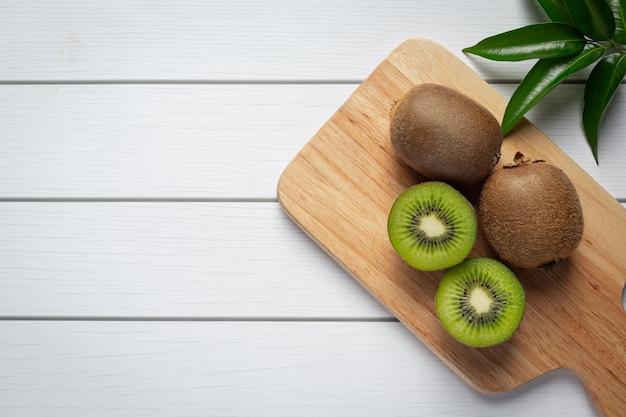 Fresh kiwi, cut into half, put on wooden cutting board Free Photo