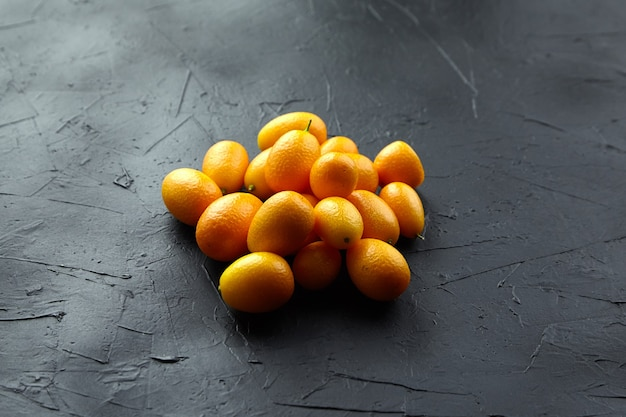 Свежие цитрусовые кумкват на черном каменном столе Premium Фотографии