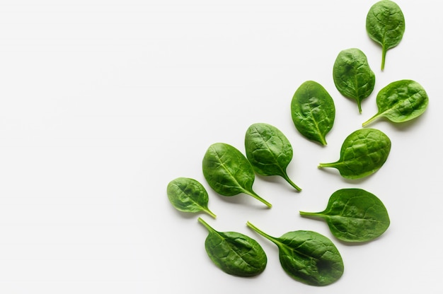 Fresh leaves of spinach are laid out on a white background in the form of a pattern. Premium Photo