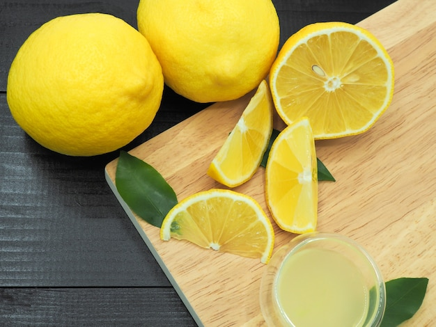 Premium Photo | Fresh lemon juice in small bowl and lemon slice on dark wood background