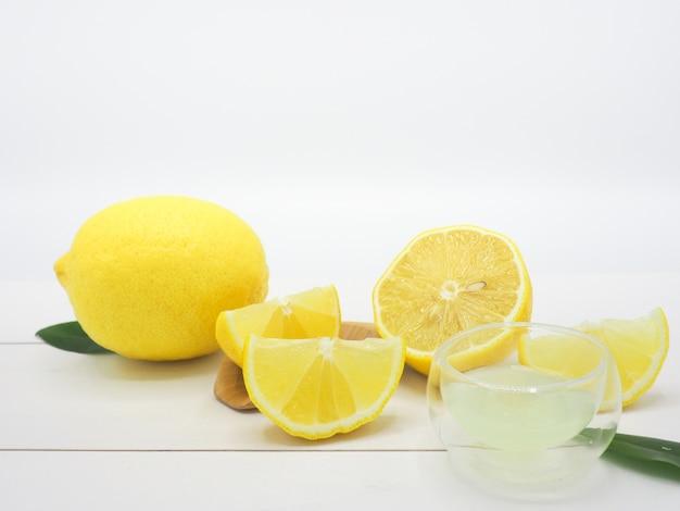 fresh lemon juice in a small bowl and lemon slice on white wood