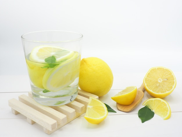 Fresh lemon in water and lemon slice on white wood background Premium Photo