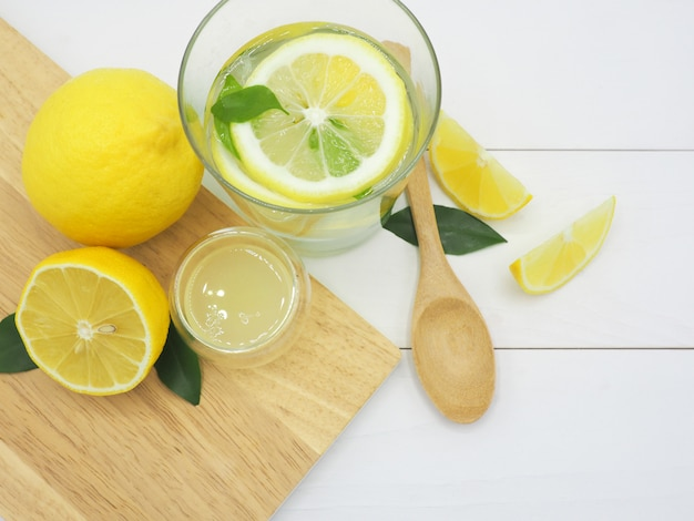 Fresh lemon in water, lemonade and lemon slice on white wood background Premium Photo