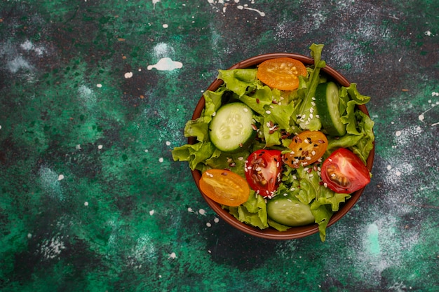 Fresh lettuce salad with yellow tomatoes, slices,cherry tomatoes,seeds bowl on dark, Free Photo