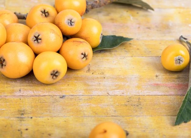 Свежие мушмулы на деревянном столе Premium Фотографии