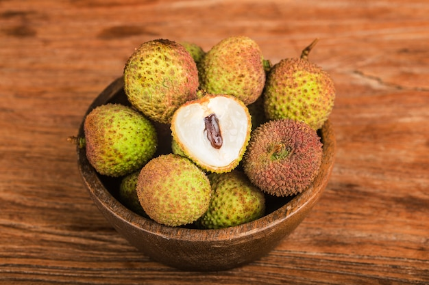 Fresh lychees on a wooden board background Premium Photo
