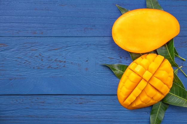 Свежее манго - красивый измельченный фрукт с зелеными листьями. концепция дизайна тропических фруктов. плоская планировка. вид сверху. Premium Фотографии
