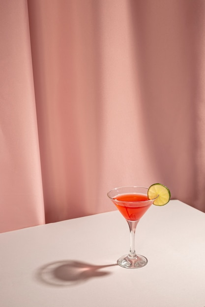 Fresh margarita cocktail drink with lemon slice on table against pink curtain Free Photo