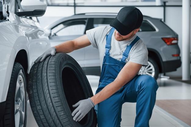 フレッシュ素材。修理ガレージでタイヤを保持しているメカニック。冬用および夏用タイヤの交換 無料写真