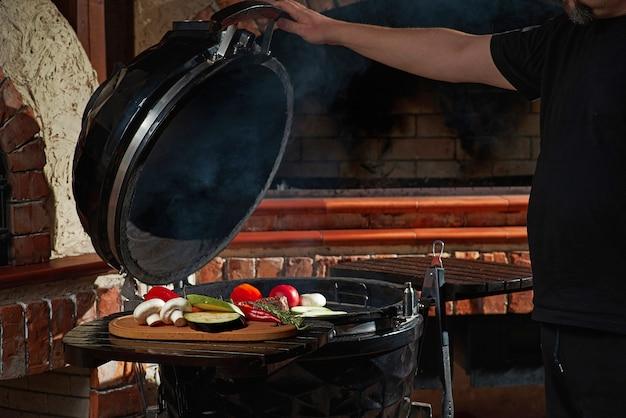 自家製の週末バーベキューで焼いた新鮮な肉と野菜。料理のコンセプト、暗いキッチン。 Premium写真