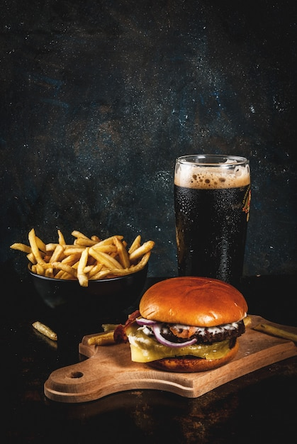 Fresh meat and cheese burger with french fries and glass of dark ginger beer, on dark blue , Premium Photo